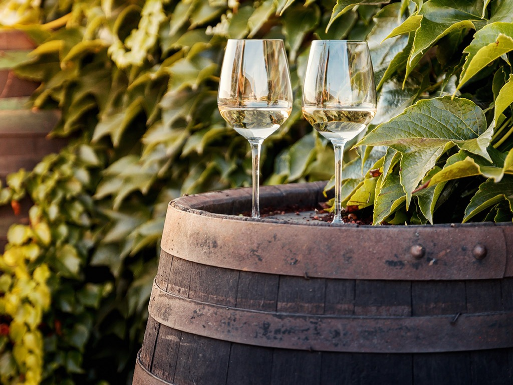 two glasses of white wine sitting on a barrel | Store-y Self Storage