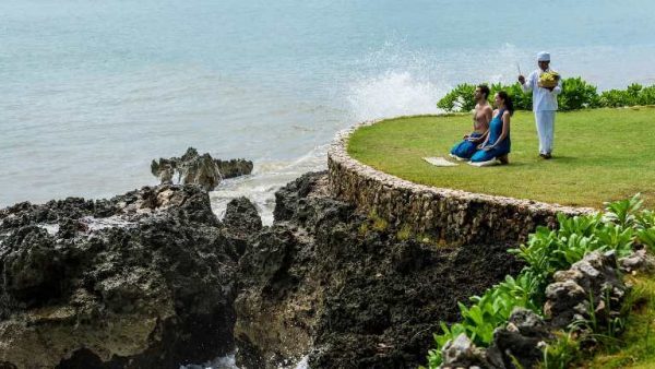 a man and a woman meditating near the shore in Bali