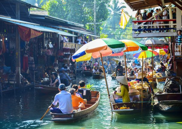 people buying food while while riding small wooden boats at saduak floating market