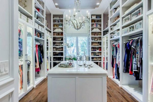 a classic walk-in closet with a chandelier