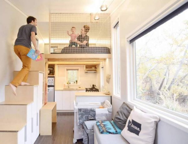 a couple playing with their baby on a loft bed