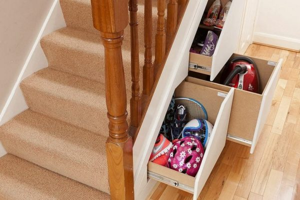 sports equipment and a vacuum stored inside understairs drawers