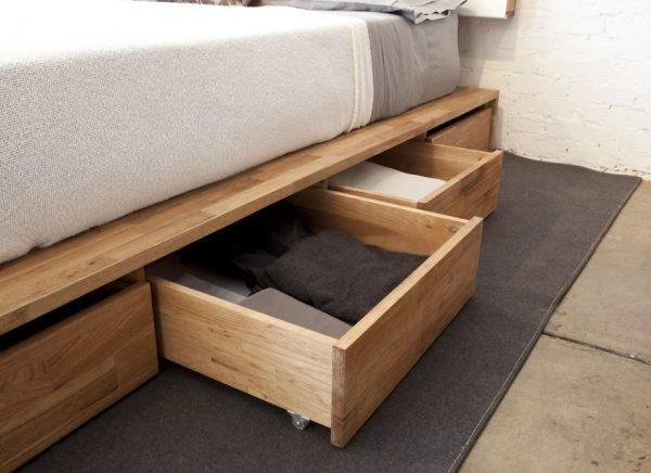 a wooden bedframe installed with drawers stuffed with fitted sheets