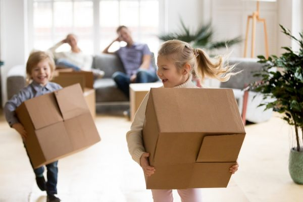 active children enjoying moving day running carrying boxes, excited kids laughing playing in new home while parents take break to rest, happy girl and boy have fun together
