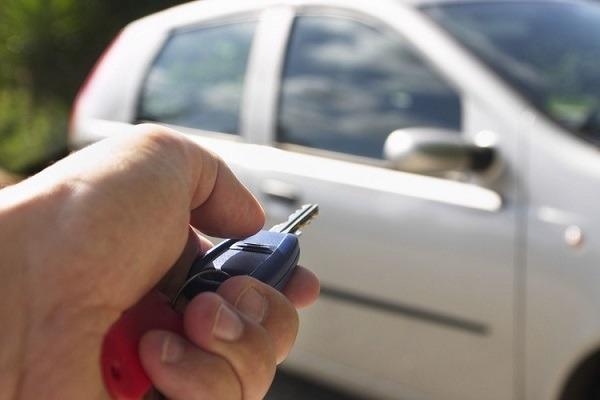 A man unlocking a car with his key