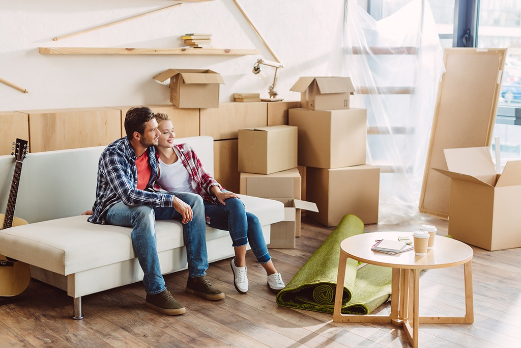 happy young couple sitting together on sofa and looking away in new house