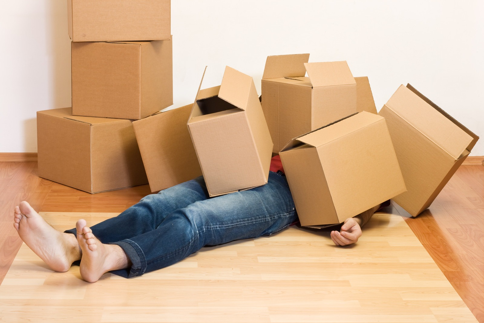 man under a pile of cardboard boxes